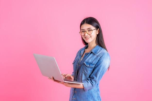 Styl życia ludzi biznesu przy użyciu komputera przenośnego na różowo