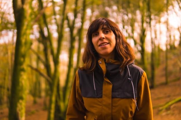 Styl życia, młoda kobieta w żółtej kurtce spacerująca po lesie jesienią. las artikutza w san sebastin, gipuzkoa, kraj basków. hiszpania