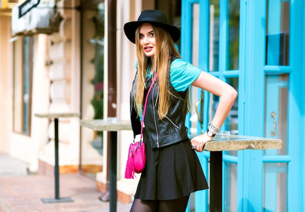 Styl życia na świeżym powietrzu portret ładnej blondynki chodzącej i cieszącej się letnim słonecznym dniem, stylowy strój, mini spódniczka, kapelusz vintage, kurtka motocyklowa, jasne detale i akcesoria, centrum miasta europa