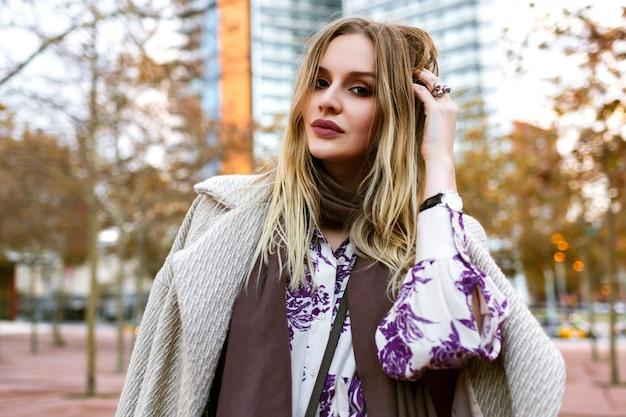 Styl życia na świeżym powietrzu pozytywny portret ładnej blondynki uśmiechniętej kobiety, która kończy się cieszyć czasem, elegancki strój glamour, ubrana w sukienkę i płaszcz, ciepłe kolory, wiosna jesień.
