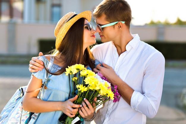 Styl życia na świeżym powietrzu przedstawiający szczęśliwą parę zakochanych, którzy dobrze się bawią i razem szaleją, uściski i pocałunki, romantyczna randka, wieczorne słońce, ulica, podróże, stylowi eleganccy faceci, piękni kochankowie.