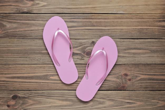 Styl życia na tropikalnej plaży. różowe klapki na podłoże drewniane. lato w tle.