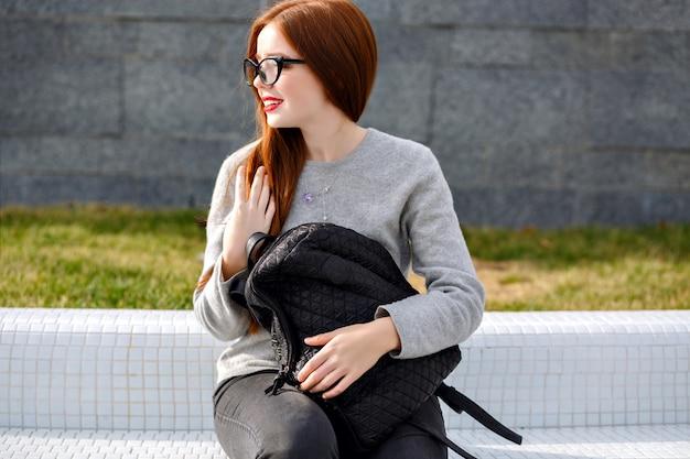 Styl życia na zewnątrz portret ładnej rudej dziewczyny na sobie przezroczyste szkło i kaszmirowy szary sweter, pozuje w parku, styl jesień zima. trzymanie plecaka.