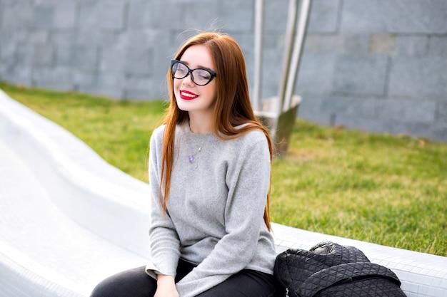 Styl życia na zewnątrz portret ładnej rudej dziewczyny na sobie przezroczyste szkło i kaszmirowy szary sweter, pozuje w parku, styl jesień zima.