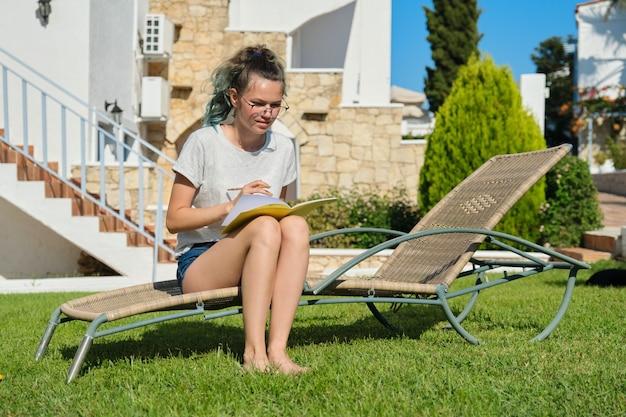Styl życia nastolatki w wieku 15, 16 lat, dziewczyny siedzącej na krześle ogrodowym na leżaku na trawie, pisze ucząc się w szkolnym zeszycie. trawnik w pobliżu domu, letni dzień