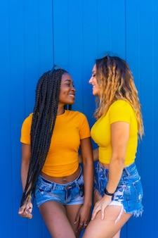 Styl życia, nastoletnie koleżanki odzwierciedlające miłość na niebieskiej ścianie ubrane w żółte koszulki. czarna dziewczyna z długimi warkoczami i blondynka kaukaska.