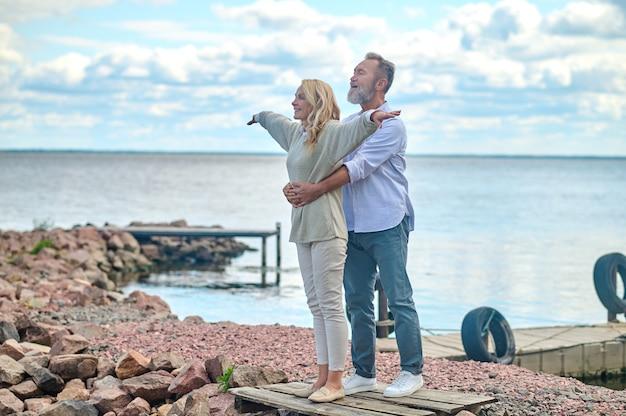 Styl życia. optymistyczny mężczyzna i kobieta w średnim wieku trzymający się za ręce do boków, stojący szczęśliwi w pobliżu morza w pogodny dzień