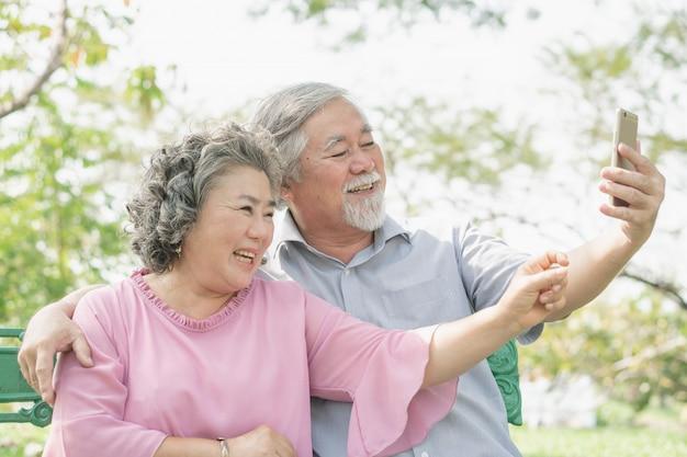 Styl życia osób starszych i technologia komunikacyjna. szczęśliwy dziadków za pomocą połączenia wideo tablet i rozmawiać z rodziną w parku.