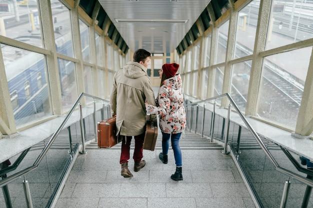 Styl życia para młodych szczęśliwych kochanków nosi na walizkach zabytkowe brązowe walizki. para stylowych wesołych biodrówek schodzących po schodach.