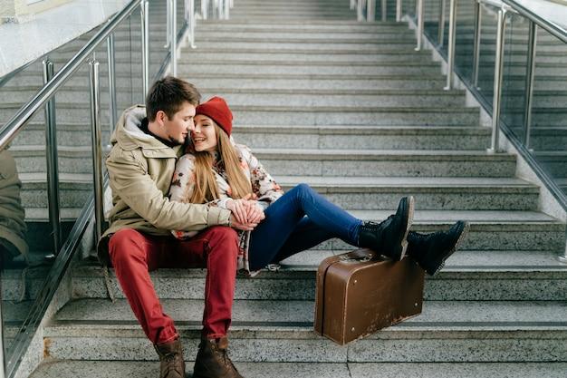 Styl życia para szczęśliwych romantycznych hipsterów w miłości. młoda para kochanków o emocjonalnych twarzach. mężczyzna z dziewczyną, walizki czekają na pociąg na schodach.
