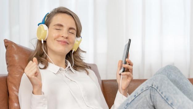 Styl życia piękna śliczna dziewczyna kobieta czuje się szczęśliwa słuchając muzyki w słuchawkach na kanapie
