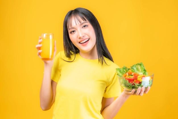 Styl życia piękne piękno azjatycka kobieta ładna dziewczyna z grzywką fryzura w żółtej koszulce czuć się szczęśliwym cieszyć się jedzeniem dieta jedzenie świeże sałatki i sok pomarańczowy dla dobrego zdrowia na białym tle na żółtym tle
