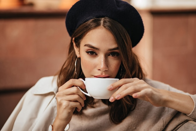 Styl życia portret eleganckiej młodej kobiety z ciemną falującą fryzurą, modnym makijażem, modnym beżowym pulowerem i płaszczem, siedzącej na tarasie kawiarni i pijącej kawę z białego kubka