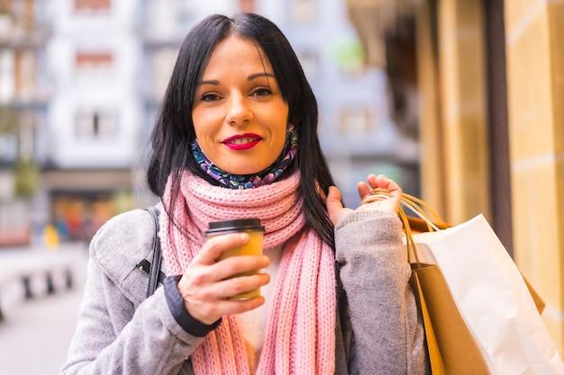 Styl życia, portret kaukaskiej brunetki robiącej zakupy w mieście z papierowymi torbami i kawą na wynos