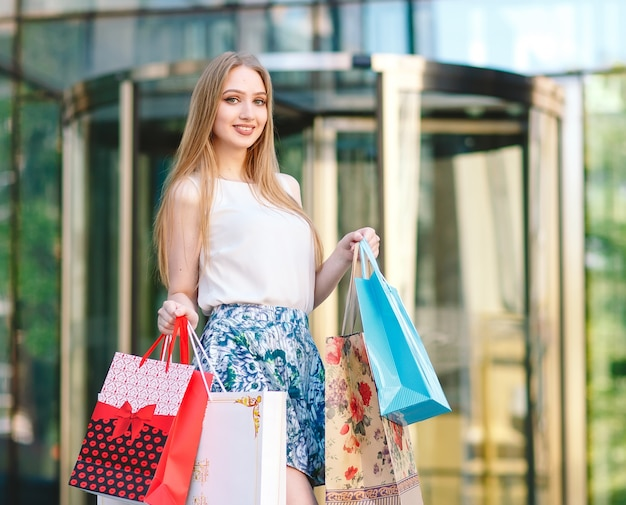 Styl życia portret młodej dziewczyny blondynka, z torby na zakupy wychodzi ze sklepu.