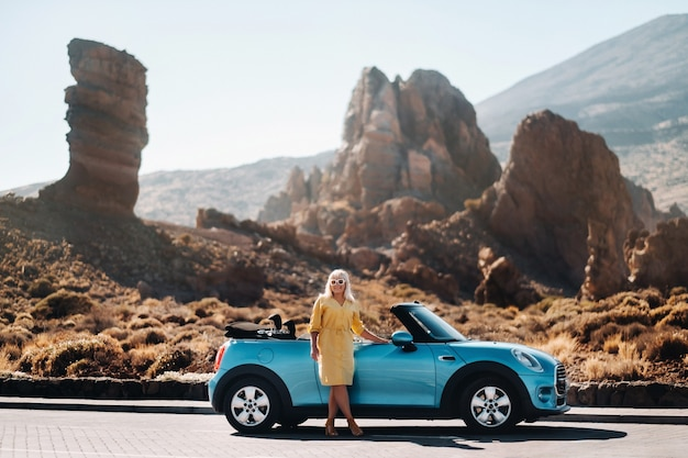 Styl życia portret młodej kobiety, cieszącej się podróżą po pustynnej dolinie, wysiadając z kabrioletu na poboczu drogi.