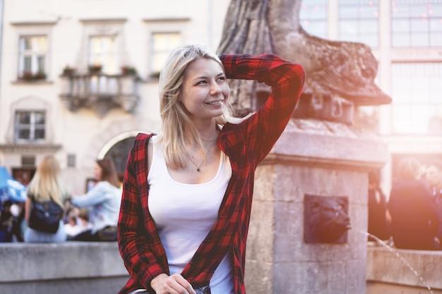 Styl życia portret modnej szczęśliwej blondynki ubranej w czerwoną rockową koszulę, białą koszulkę bawiącą się na świeżym powietrzu w mieście