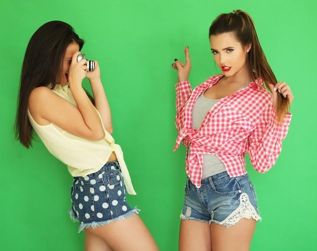 Styl życia portret pięknych najlepszych przyjaciółek hipster dziewcząt stojących razem z aparatem fotograficznym i bawić się podczas robienia zdjęcia. na zielonym tle.