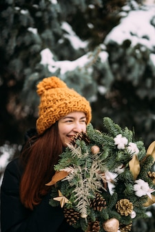 Styl życia portret uśmiechający się tysiącletnia dziewczyna w pomarańczowym kapeluszu. śnieżny dzień bożego narodzenia