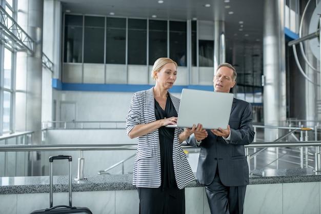 Styl życia. poważny biznes dobrze wyglądający kobieta i mężczyzna stojący w pobliżu walizki patrzący na laptopa na lotnisku czekający na odlot