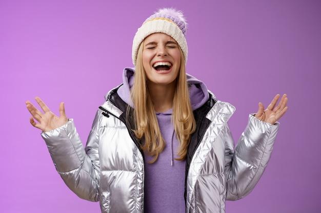 Styl życia. radosna szczęśliwa blond kobieta wolna emocje wrzeszczy radośnie bawiąc się, ciesząc się niesamowitym dniem, uśmiechając się szeroko unosząc ręce w górę triumfując świętując osiągnięcie wygranej marzenie.