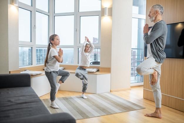 Styl życia. siwowłosy brodaty tata i słodkie dzieci stoją unosząc jedną nogę w pozie jogi w domu w nowoczesnym jasnym pokoju