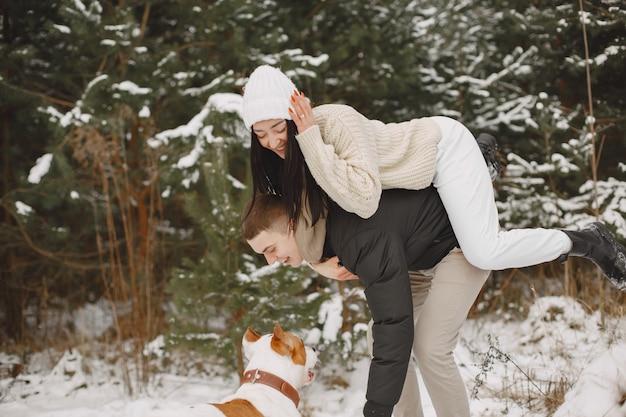 Styl życia strzał para w śnieżnym lesie z psem