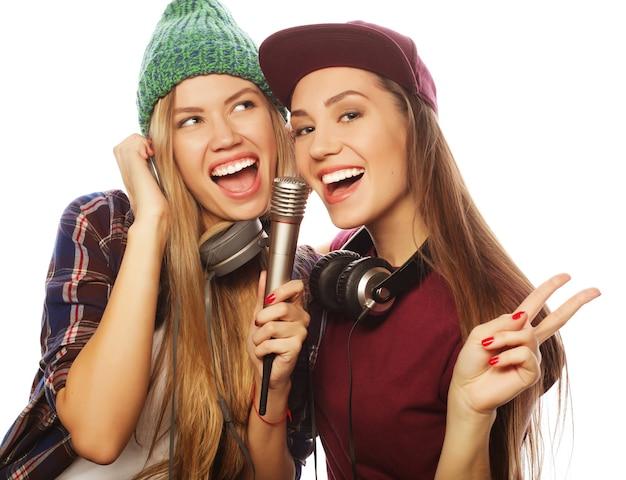 Styl życia, szczęście, emocje i koncepcja ludzi: dwie piękne hipsterki z mikrofonem śpiewają i dobrze się bawią