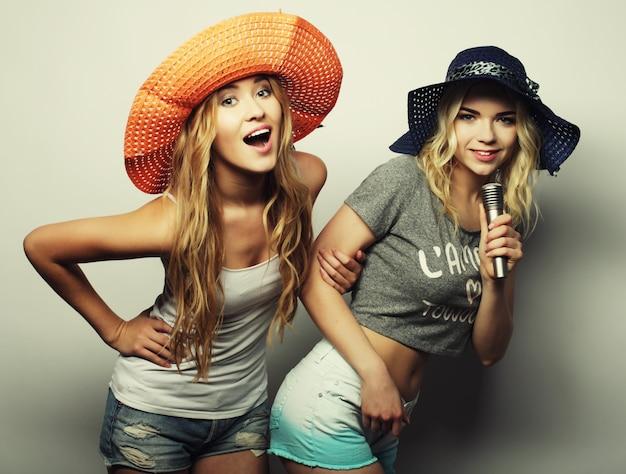 Styl życia, szczęście, emocje i koncepcja ludzi: dwie piękności z mikrofonem śpiewają i bawią się