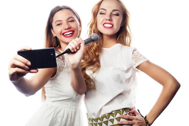 Styl życia, szczęście, emocje i koncepcja ludzi: piękne dziewczyny z mikrofonem śpiewają i robią selfie