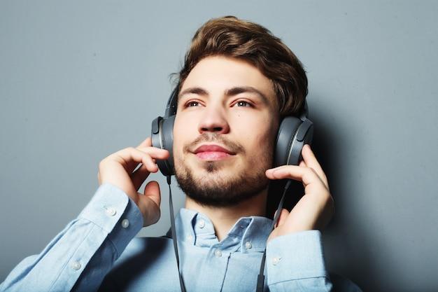 Styl życia, szczęście, emocje i koncepcja ludzi: radość z jego ulubionej muzyki. szczęśliwy młody stylowy mężczyzna dostosowując jego reklama słuchawki uśmiechając się stojąc przed szarej przestrzeni