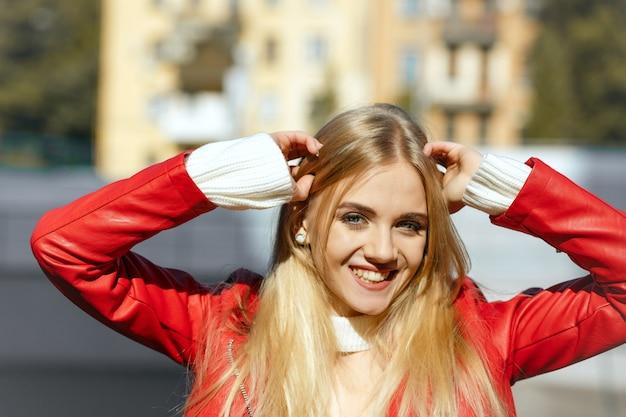 Styl życia: szczęśliwy uśmiechnięty model w czerwonej skórzanej kurtce pozujący na ulicy w promieniach słońca