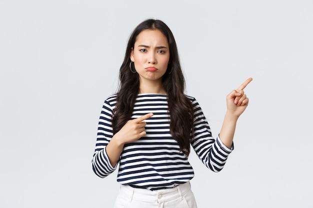 Styl życia, uroda i moda, koncepcja emocji ludzi. rozczarowana zdenerwowana młoda azjatycka kobieta dąsa się i marszczy brwi z niezadowoleniem, wskazując palcami prawą górę jako narzekającą na produkt lub usługę