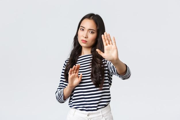 Styl życia, uroda i moda, koncepcja emocji ludzi. zirytowana kobieta czuje się nieswojo, gdy jest fotografowana, prosi o wyłączenie aparatu, podnosząc ręce do góry, chroniąc twarz przed latarką
