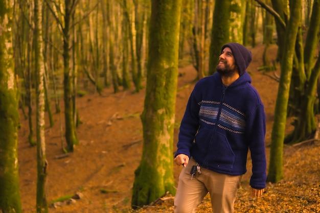 Styl życia, uśmiechnięty młody człowiek w niebieskim wełnianym swetrze i kapeluszu, cieszący się jesienią w lesie. las artikutza w san sebastin, gipuzkoa, kraj basków. hiszpania