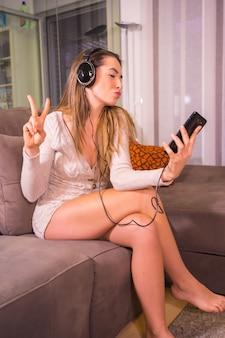 Styl życia w domu, młoda kobieta rasy kaukaskiej, słuchanie listy odtwarzania muzyki ze słuchawkami na kanapie w domu