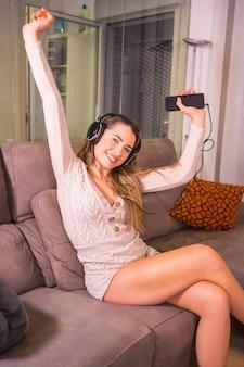 Styl życia w domu, portret blondynki rasy kaukaskiej uśmiechniętej i tańczącej do playlisty ze słuchawkami na kanapie w domu