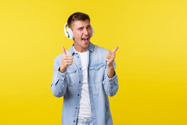 Styl życia, wakacje, koncepcja technologii. podekscytowany przystojny szczęśliwy blondyn wibrujący, relaksujący się niesamowitą muzyką, mający na sobie słuchawki i pokazujący kciuki w górę z aprobatą, żółte tło.