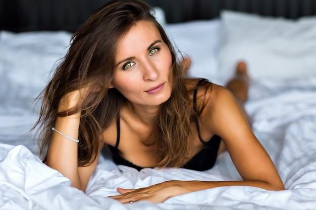 Styl życia z bliska portret wspaniałej pięknej brunetki, idealna skóra, naturalny makijaż, oliwkowe oczy, opalona skóra, delikatny pastelowy kolor, relaks w jej salonie, w bieliźnie, poranek.