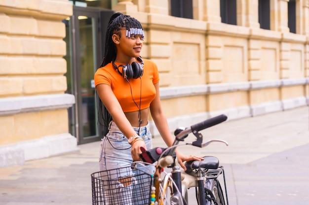 Styl życia z młodą tancerką trap w mieście. czarna dziewczyna z afrykańskiej grupy etnicznej z pomarańczowym t-shirtem i kowbojskimi spodniami. cofing rower zaparkowany w mieście