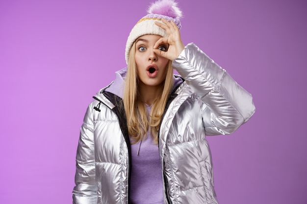 Styl życia. zafascynowana rozbawiona młoda atrakcyjna blond dziewczyna wakacje śnieżny wiejski wygląd zdumiony pod wrażeniem pokaż okay znak ok wow składane usta w stylowej srebrnej błyszczącej kurtce, dysząc zdumiony.