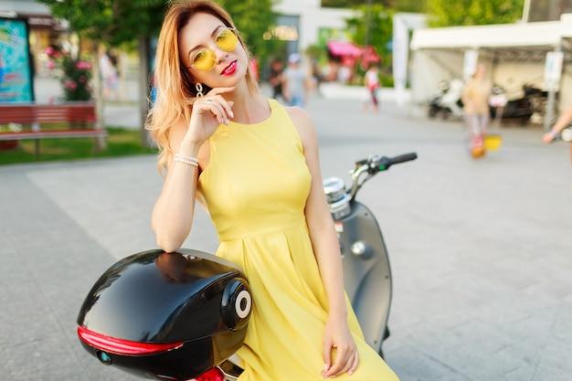 Styl życia zewnątrz portret stylowej kobiety w żółtej sukience vintage, siedzącej na czarnym motocyklu electro.