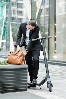 Stylidh młody przedsiębiorca z hulajnogą, szukający dokumentu w skórzanej torbie podczas rozmowy telefonicznej z kolegą