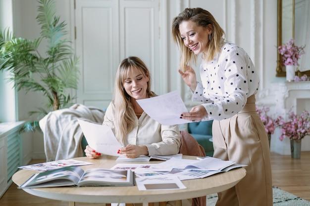 Styliści projektantów mody pracujący nad nowym projektem w studio, używając laptopa, czasopism, szkiców. dwa młoda kobieta ono uśmiecha się dyskutujący pomysły.