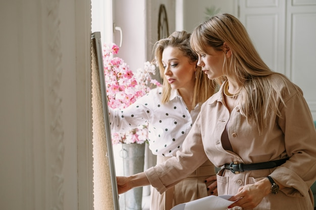 Styliści projektantów mody pracujący nad nowym projektem w studio, wykorzystujący biurko, czasopisma, szkice. dwa młoda kobieta ono uśmiecha się dyskutujący pomysły.