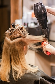 Stylista fryzjerski suszy mokre włosy suszarką do włosów