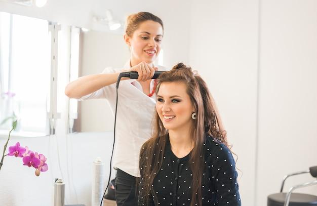 Stylista suszenia włosów klientki w salonie kosmetycznym.