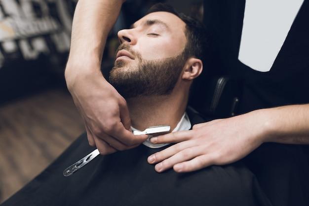 Stylista używa klasycznej ostrej brzytwy, starannie goląc klienta.