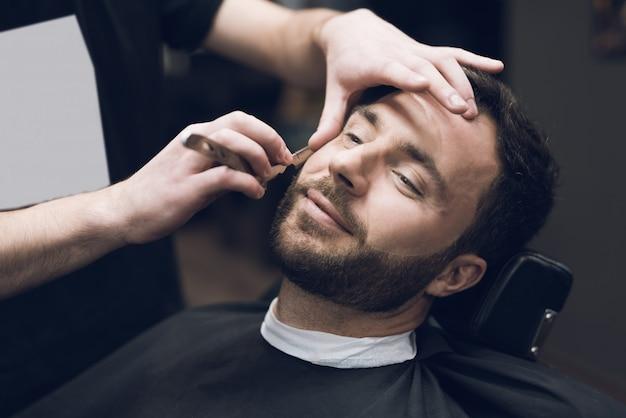 Stylista używa klasycznej ostrej brzytwy, starannie golącej klienta.