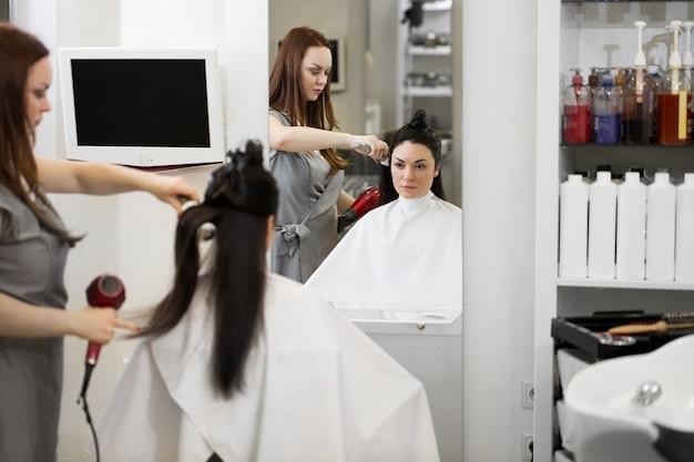 Stylista włosów pracuje nad fryzurą kobiety w salonie. suszenie długich brązowych włosów suszarką i okrągłą szczotką